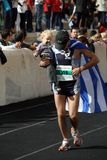 27th Athens Classic Marathon Moments. Anonymous runner holding his child runs tiredly towards the finish line Stock Photos