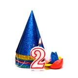 2nd birthday. Image with number two candle, party hats and balloons on white background Stock Photography