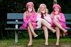3个吃的棒棒糖姐妹 库存图片
