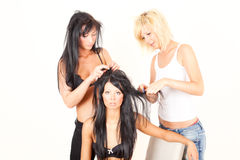 3个朋友女孩头发帮助的批次 库存照片
