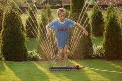 3个男孩儿童庭院喷水隆头 库存图片
