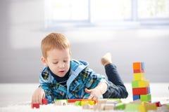 3 éénjarigen die met kubussen op vloer spelen Stock Foto