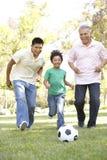 3 οικογενειακό παίζοντας ποδόσφαιρο γενεάς στο πάρκο στοκ εικόνα