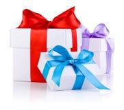3 белых коробки связали красную, пурпуровую и голубую тесемку Стоковые Фотографии RF