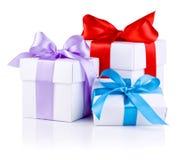 3 белых коробки с красной, пурпуровой и голубой тесемкой Стоковые Изображения