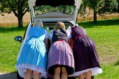 3 девушки в Dirndl смотря в автомобил-ботинке Стоковые Фото