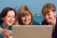 3 девушки с компьтер-книжкой Стоковое фото RF