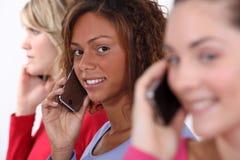 3 женщины используя мобильные телефоны стоковая фотография rf
