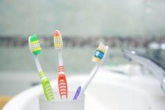 3 зубной щетки в ванной комнате. Стоковые Изображения RF