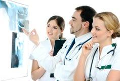 3 молодых медицинских работника смотря рентгеновские снимки Стоковое Изображение