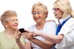 3 пожилых женщины с мобильным телефоном. Стоковое фото RF