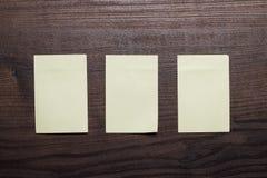 3 пустых стикера на коричневой деревянной таблице Стоковые Фотографии RF