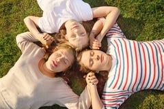3 руки и лож владением девушок на траве. Стоковое фото RF