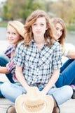 3 счастливых девушки сидя совместно outdoors Стоковые Изображения RF