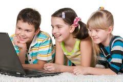 жизнерадостная компьтер-книжка 3 малышей использующ стоковая фотография