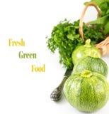 3 круглых цукини в ряд с старым ножом, густолиственными зелеными цветами Стоковое фото RF