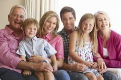 Семья 3 поколений ослабляя на софе дома Стоковое фото RF