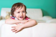 3 años felices de bebé que se sienta en el sofá blanco de cuero Foto de archivo