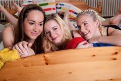 3 amigas adoráveis que afagam em uma cama Fotografia de Stock Royalty Free