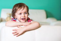 3 anni felici di neonato che si siede sul sofà bianco di cuoio Fotografia Stock