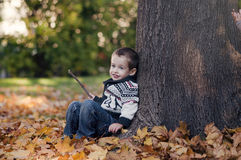 3 anos de criança idosa que senta-se na folha dourada Fotos de Stock Royalty Free