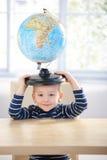 3 ans adorables ayant l'amusement avec le sourire de globe Photo stock