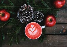 3 Apples and 2 Pine Cones With Cup of drink on Table Royalty Free Stock Photography