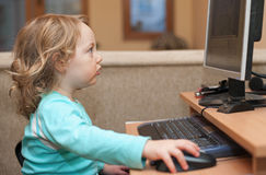 3 behandla som ett barn datorskrivbordsflickan little som använder Royaltyfri Foto