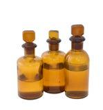 3 bottiglie chimiche marroni piene a metà Immagine Stock