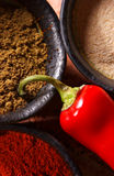 3 bowls filled with spices and a red chili pepper Stock Image