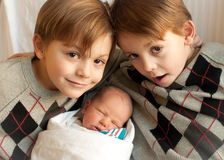 3 brothers. Twin boys pose with a newborn baby brother in the hospital Stock Photos