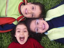 3 Children. Three smiling children lying on the grass Stock Photos