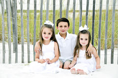 3 Children on the Beach Too. 3 Children sitting in the sand by the shore in front of a wooden fence wearing white in their barefeet Royalty Free Stock Images