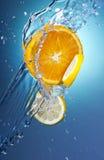 3 citrusa skivor plaskar vatten Royaltyfri Fotografi