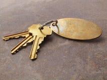 3 claves y keychain en el azulejo Imagen de archivo libre de regalías