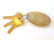 3 clés d'or et keychain blanc sur le blanc Image libre de droits