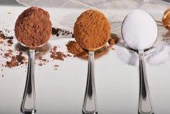 3 cuillères avec des ingrédients de traitement au four Photo stock