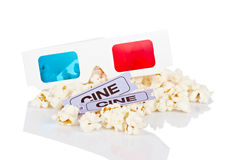 3-D anaglyph glasses, popcorn and two tickets. Reflected on white background. Shallow depth of field Royalty Free Stock Photos