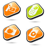 3-D electronics icons. A collection of four three-dimensional orange or green icons or buttons with symbols for electronic devices Stock Photo