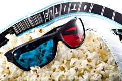3-D glasses on popcorn heap with film strip. 3-D red blue glasses on popcorn heap with film strip in the background Royalty Free Stock Image