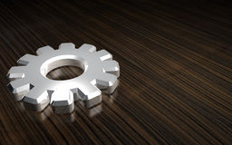 3-D metal gear on wood. A shiny metallic gear on a wood grain background Stock Image