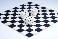 3 dados en un tablero de ajedrez, aislado en un fondo blanco Imagen de archivo libre de regalías