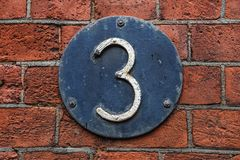 Free 3 Digit On Dark Metal Background On Red Brick Wall. Royalty Free Stock Image - 100066586