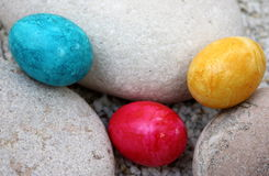 3 easter eggs. Coloured easter eggs and stones Royalty Free Stock Photo