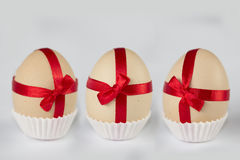 3 Easter Special Offer Eggs. 3 Easter eggs with red ribbons in paper saucer Royalty Free Stock Image