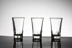 3 Empty Glasses with light. 3 Empty and clear Glasses reflecting on light background Stock Image