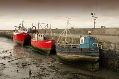 3 Fishing Boats At Low Tide Howth. Three fishing boats left high and dry in the harbour Royalty Free Stock Photos