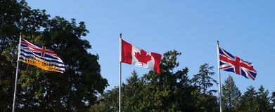 3 Flags. Canadian flag flanked by the union jack and BC provincial flag Royalty Free Stock Images