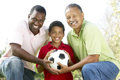 3 generaciones en parque con el balón de fútbol Fotos de archivo