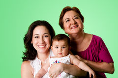 3 Generations of women. Beautiful happy three 3 generations of Caucasian Hispanic Latina women, grandmother, mother and baby girl, on green - mothers day concept